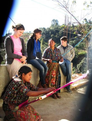 Alumna Nikki Brand's GPP Practice Experience in Panajachel, Guatemala, inspired her to pursue a career in community development in Latin America. Here, Brand (seated, center) listens as her Guatemalan co-worker, Juana, tells students and interns her incredible life story while Juana's sister Marcela demonstrates traditional backstrap weaving. Photo credit: Nikki Brand