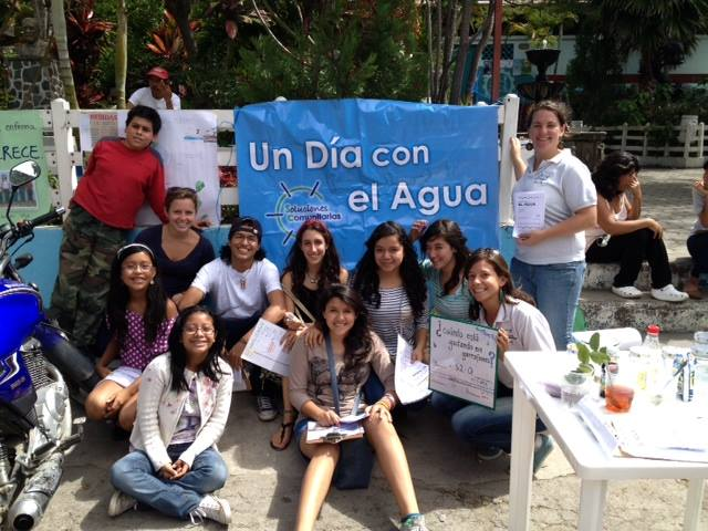 "Brand (front right, holding sign) poses with student volunteers from a local high school at ""Un Dia Con el Agua"" (A Day With Water) in Panajachel – an educational event about the importance of water and to promote water filters. Brand made many lasting friendships during her Practice Experience that she rekindled while working with Community Enterprise Solutions. Photo credit: Nikki Brand"